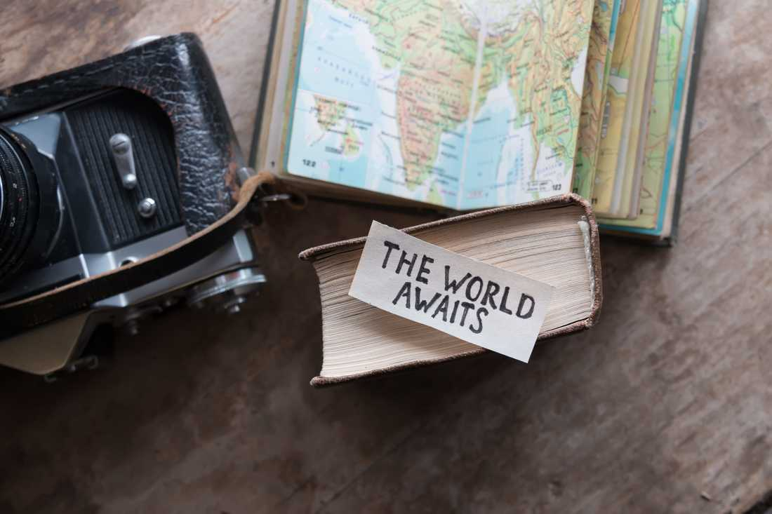 camera, map, and piece of paper that says 'The World Awaits'