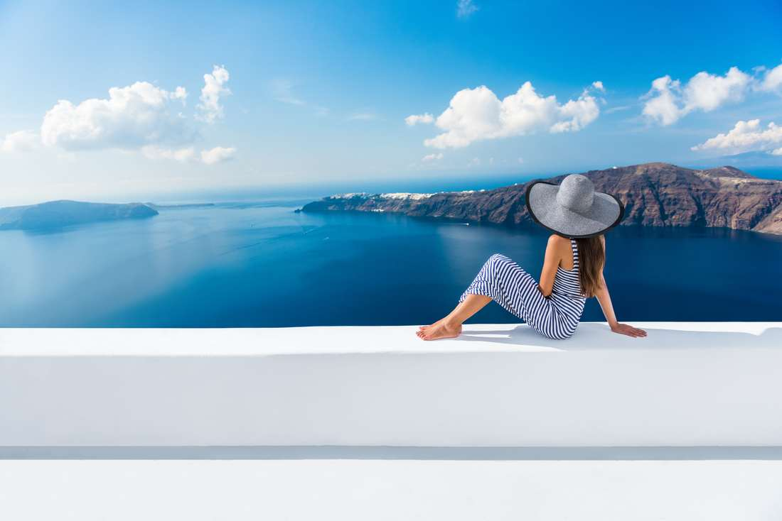 women louging on white wall with blue water and mountain in background